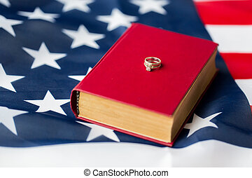 close up of american flag, wedding rings and bible - civil...