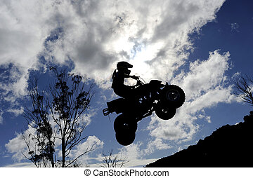A silhouette of a quad bike ATV jumping through a cloudy sky...