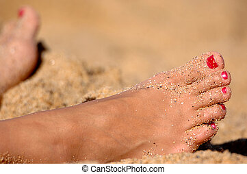 A young womans feet with painted nails resting in the sand...