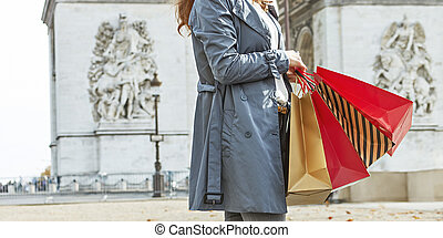 happy trendy woman in trench coat shopping in Paris, France...