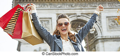 smiling woman with shopping bags in Paris, France rejoicing...