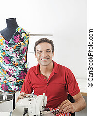 Happy Male Tailor Sitting By Mannequin In Sewing Factory -...