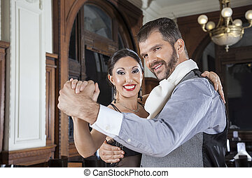 Portrait Of Happy Man And Woman Performing Tango In Restaurant