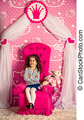 beautiful little curly girl in a big soft chair, kids...