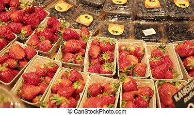 Showcases with strawberries, blueberries and black currants...