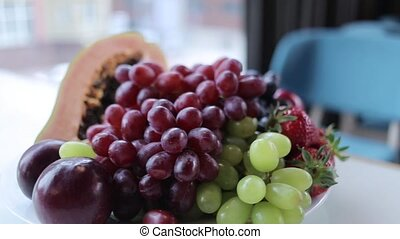 composition with grapes, papaya, strawberries and a glass of...