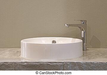ceramic washbasin and metal faucet in bathroom