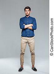 Handsome young casual man standing with hands crossed over...