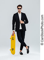 Businessman in sunglaasses leaning on skateboard with legs crossed