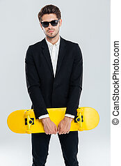 Attractive young businessman in black suit holding yellow skateboard