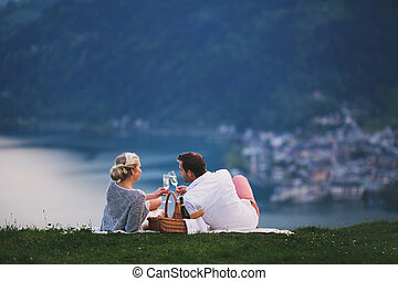 Romantic picnic on the hillside - Young couple lying on the...