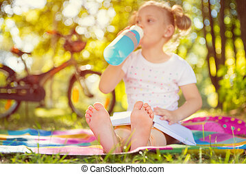 Cute child sitting on grass with book. Foots in focus - Cute...