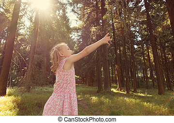 Cute little child girl reach branch in summer forest. Rays...