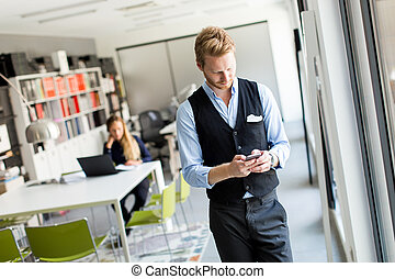Mann with mobile phone in office - Young redhead man in the...