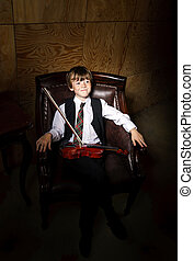 Freckled red-hair boy with violin sitting in the arm-chair -...
