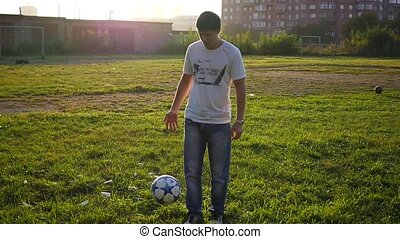 man practicing with a ball on the soccer field in slowmotion