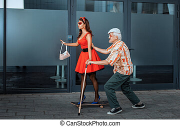 Old man teaches to ride a skateboard young girl. - Old man...
