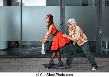 Old man pushes a woman. - Old man pushing a woman on a...