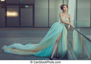 Woman in a long dress standing - A young girl is, she is...