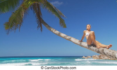 relaxing on palmtree close - woman in white bikini sitting...