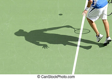 The shadow of a man playing tennis on a court.