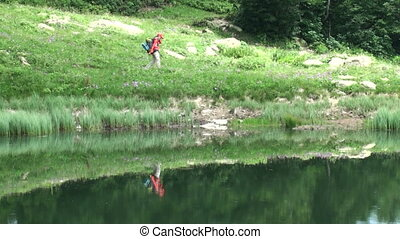 Woman with backpack hiker walking along the lake in the...