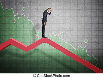 Businessman standing on falling diagram and peering into the...