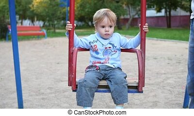 a child swinging on a swing on the Playground