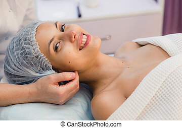 beautiful young woman lying relaxed in a spa salon and...