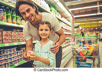 Dad and daughter in the supermarket - Handsome young father...