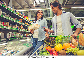 Couple in the supermarket - Beautiful young couple is...