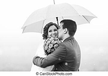Just married couple have fun under umbrella