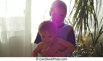 children hug and play at home in the sun