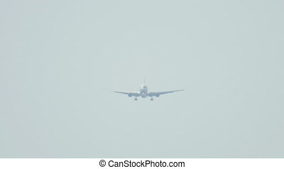 Widebody airplane approaching over ocean before landing in...