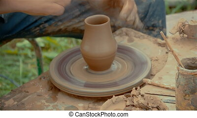 Hands shaping a clay pot on pottery wheel.