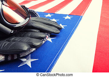 Ski goggles and gloves over USA flag - close up shot