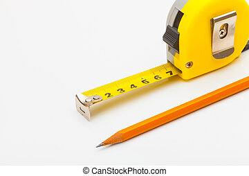 Measure tape with pencil and gloves near it - Yellow measure...