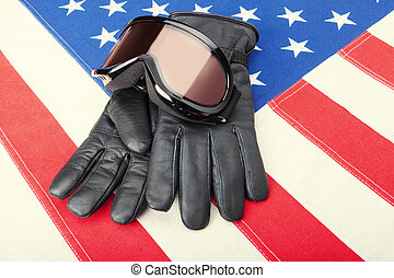 Ski goggles and gloves over USA flag - close up studio shot