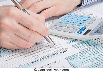 A man filling out USA Tax 1040 Form with dollars and...