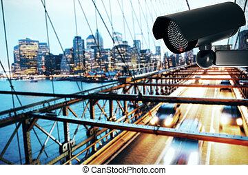 Black security camera on city background