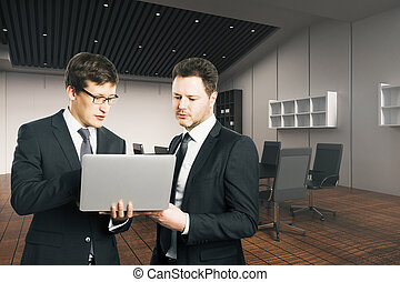 Teamwork concept - Two young businesspeople with laptop...