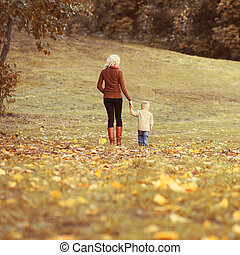 Happy family mother and child walking together in autumn park