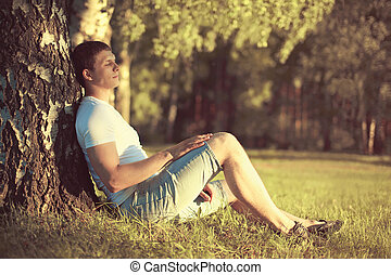 Relaxing man sitting under a tree with eyes closed meditating and enjoying the warm evening sunset in profile