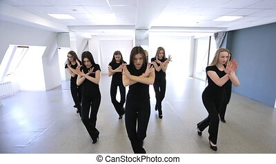 Young women are repeating dance movements in model school....