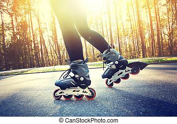 Teenage girl on roller skates at summer. Inline skates sport...