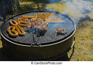 Roast large chunks of meat and sausage on a large grill