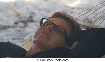 shot transition senior businesswoman sleeping in hammock