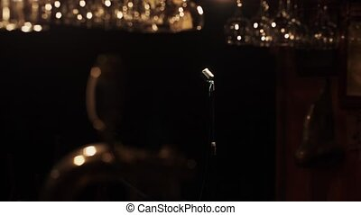 Bar stand of empty retro club. Vintage microphone stand on stage under spotlight
