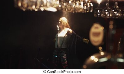 Scrubwoman in gloves dance sing on stage in vintage microphone under spotlight