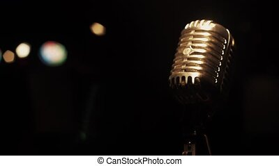 Concert metal microphone stand on stage in empty retro club. Spotlights.